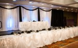 Sweetheart table for the Bride & Groom on stage. Bridal Party is setup on ground level.          Photo Credit: Heather Bellini